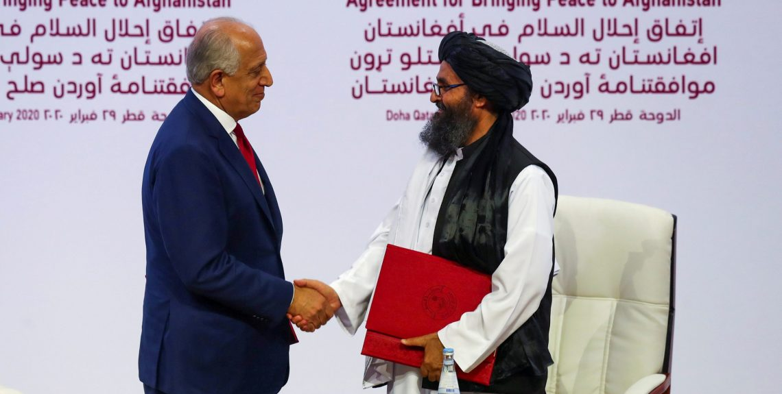 Mullah Abdul Ghani Baradar, the leader of the Taliban delegation, and Zalmay Khalilzad, U.S. envoy for peace in Afghanistan, shake hands after signing an agreement at a ceremony between members of Afghanistan's Taliban and the U.S. in Doha, Qatar February 29, 2020. REUTERS/Ibraheem al Omari - RC2LAF91DVTE